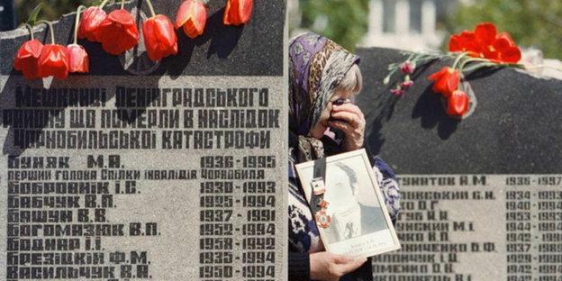 """ARCHIV - Eine Angehörige eines Tschernobyl-Opfers steht zwischen Gedenksteinen in Kiew am 26.04.1999 während einer Gedenkveranstaltung. Am 26. April 1986 kam es im Kernkraftwerk Tschernobyl zum Super-GAU. Der Reaktormantel explodiert, Trümmer und radioaktives Material werden nach außen geschleudert, eine nukleare Wolke breitet sich über weite Teile Europas aus. Das Umfeld des Kraftwerks ist bis heute Sperrgebiet. Im Jahr 2011 - dem Jahr des Nuklearunfalls von Fukushima - jährt sich die Katastrophe zum 25. Mal. Foto:EPA/dpa (zu dpa-Themenpaket """"25 Jahre Tschernobyl"""" vom 13.04.2011) +++(c) dpa - Bildfunk+++"""
